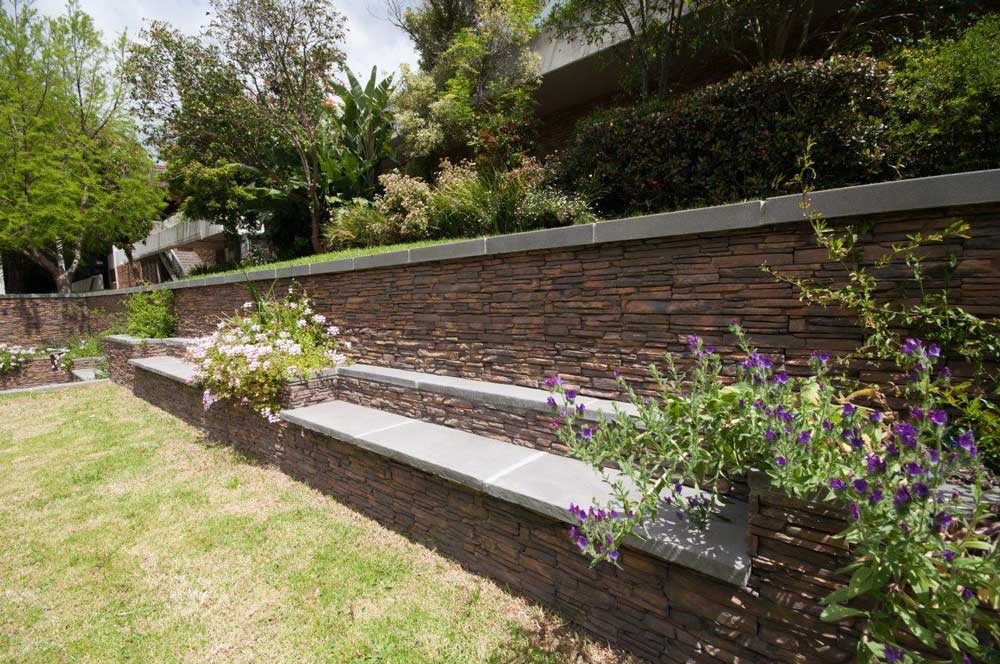 One of the retaining wall benches dressed with Saxon Split Cladding and topped with Kent Random Edge paving.